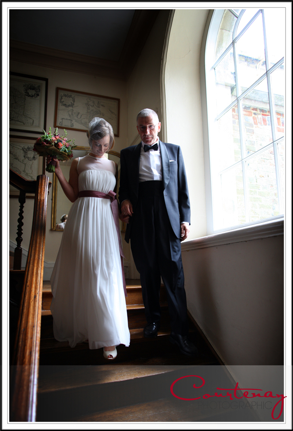 Bride decends the grand staircase at smedmore house dorset