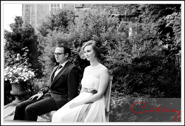 Bride and groom sit at ceremony in smedmore house gardens