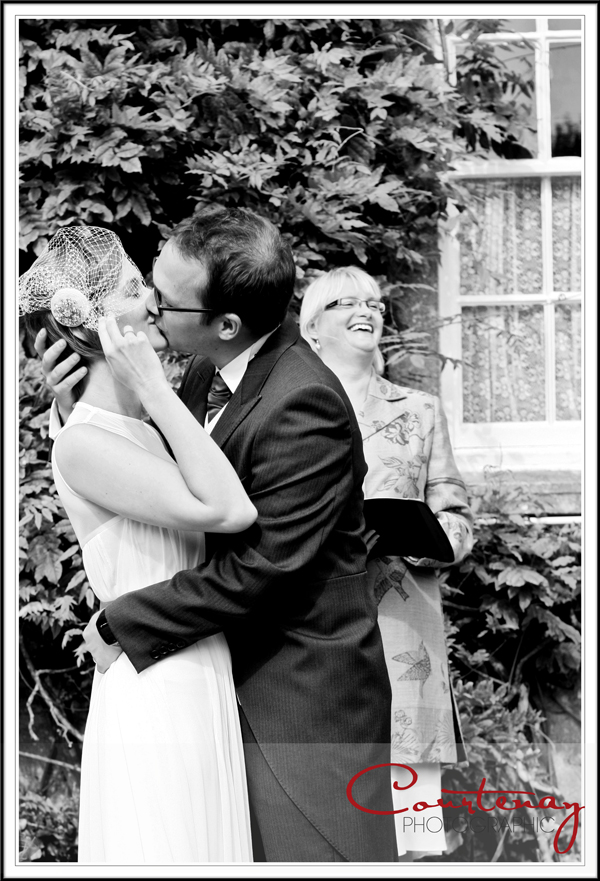 Bride and groom first kiss in smedmore house gardens